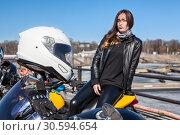 Купить «White crash helmet on motorcycle handlebars and woman passenger not in focus on background», фото № 30594654, снято 6 апреля 2019 г. (c) Кекяляйнен Андрей / Фотобанк Лори
