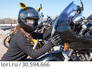 Купить «Biker girl in helmet and mask embracing plastic front cowl with headlight of her motorcycle, looking at camera», фото № 30594666, снято 6 апреля 2019 г. (c) Кекяляйнен Андрей / Фотобанк Лори