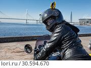 Купить «Pretty biker girl in leather jacket and black helmet with mask on face looking back while sitting in motorcycle», фото № 30594670, снято 6 апреля 2019 г. (c) Кекяляйнен Андрей / Фотобанк Лори
