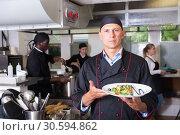 Купить «Chef holding finished dish», фото № 30594862, снято 24 сентября 2018 г. (c) Яков Филимонов / Фотобанк Лори