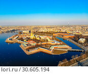 Купить «Beautifull aerial view of the Petropavlovsky fortress in sunny spring day. Golden tall spire of famous Peter and Paul Cathedral on the blue sky background. Historical centre of St. Petersburg, Russia.», фото № 30605194, снято 4 апреля 2019 г. (c) Алексей Ширманов / Фотобанк Лори