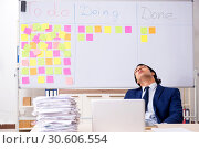 Купить «Young handsome employee in front of whiteboard with to-do list», фото № 30606554, снято 16 октября 2018 г. (c) Elnur / Фотобанк Лори