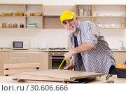 Купить «Aged contractor repairman working in the kitchen», фото № 30606666, снято 20 декабря 2018 г. (c) Elnur / Фотобанк Лори