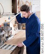 Купить «Male joiner adjusting chipboard at workplace», фото № 30607050, снято 7 ноября 2016 г. (c) Яков Филимонов / Фотобанк Лори