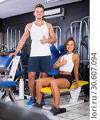 Купить «Smiling young man and woman taking pause between exercising in gym», фото № 30607094, снято 22 апреля 2019 г. (c) Яков Филимонов / Фотобанк Лори