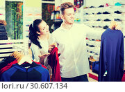 Купить «Happy loving couple deciding on new sportswear», фото № 30607134, снято 22 ноября 2016 г. (c) Яков Филимонов / Фотобанк Лори