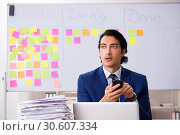 Купить «Young handsome employee in front of whiteboard with to-do list», фото № 30607334, снято 16 октября 2018 г. (c) Elnur / Фотобанк Лори