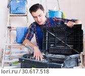 Builder handyman choosing tool in toolbox. Стоковое фото, фотограф Яков Филимонов / Фотобанк Лори