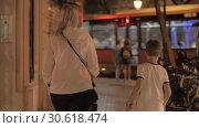 Купить «A woman with a baby carriage and with an elder son walking down the evening street», видеоролик № 30618474, снято 23 августа 2019 г. (c) Данил Руденко / Фотобанк Лори