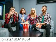 Friends eating popcorn and having fun in cinema. Стоковое фото, фотограф Tryapitsyn Sergiy / Фотобанк Лори
