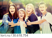 Купить «Portrait of four teenagers standing and holding thumbs up together outdoors», фото № 30618754, снято 21 июля 2019 г. (c) Яков Филимонов / Фотобанк Лори