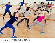 Купить «vigorous teenage boys and girls learning in dance hall», фото № 30618850, снято 26 апреля 2017 г. (c) Яков Филимонов / Фотобанк Лори