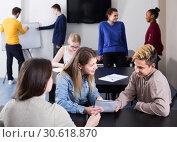 active classmates having animated talks at break between classes. Стоковое фото, фотограф Яков Филимонов / Фотобанк Лори