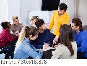 Fellow students having group work tasks during school day. Стоковое фото, фотограф Яков Филимонов / Фотобанк Лори
