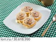 Купить «Rolled cinnamon buns on white plate», фото № 30618990, снято 23 сентября 2019 г. (c) Яков Филимонов / Фотобанк Лори