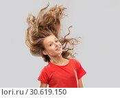 Купить «smiling teenage girl in red with long wavy hair», фото № 30619150, снято 17 февраля 2019 г. (c) Syda Productions / Фотобанк Лори