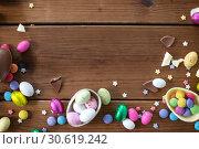 Купить «chocolate eggs and candy drops on wooden table», фото № 30619242, снято 22 марта 2018 г. (c) Syda Productions / Фотобанк Лори