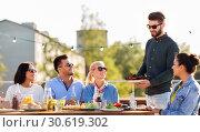 Купить «friends at bbq party on rooftop in summer», фото № 30619302, снято 2 сентября 2018 г. (c) Syda Productions / Фотобанк Лори