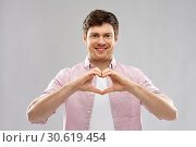 Купить «man making hand heart gesture over gey background», фото № 30619454, снято 3 февраля 2019 г. (c) Syda Productions / Фотобанк Лори