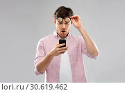 Купить «embarrassed young man looking at smartphone», фото № 30619462, снято 3 февраля 2019 г. (c) Syda Productions / Фотобанк Лори