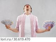 Купить «screaming young man with euro and dollar money», фото № 30619470, снято 3 февраля 2019 г. (c) Syda Productions / Фотобанк Лори