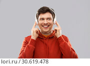 happy young man in headphones and red hoodie. Стоковое фото, фотограф Syda Productions / Фотобанк Лори