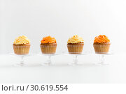 Купить «cupcakes with frosting on confectionery stands», фото № 30619554, снято 6 июля 2018 г. (c) Syda Productions / Фотобанк Лори