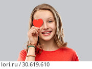 Купить «smiling teenage girl covering eye with red heart», фото № 30619610, снято 17 февраля 2019 г. (c) Syda Productions / Фотобанк Лори