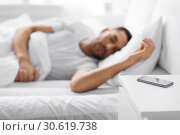 Купить «smartphone on bedside table near sleeping man», фото № 30619738, снято 6 мая 2017 г. (c) Syda Productions / Фотобанк Лори