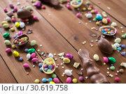 Купить «chocolate eggs and candy drops on wooden table», фото № 30619758, снято 22 марта 2018 г. (c) Syda Productions / Фотобанк Лори