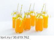 Купить «orange juice in glass bottles with paper straws», фото № 30619762, снято 6 июля 2018 г. (c) Syda Productions / Фотобанк Лори