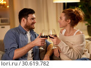 Купить «happy couple drinking red wine at home in evening», фото № 30619782, снято 5 января 2019 г. (c) Syda Productions / Фотобанк Лори