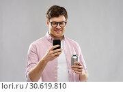 Купить «young man in glasses with smartphone and drink», фото № 30619810, снято 3 февраля 2019 г. (c) Syda Productions / Фотобанк Лори