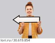 Купить «red haired teenage girl with arrow showing to left», фото № 30619854, снято 28 февраля 2019 г. (c) Syda Productions / Фотобанк Лори