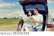 happy man and woman with road map at hatchback car. Стоковое фото, фотограф Syda Productions / Фотобанк Лори