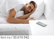 Купить «smartphone on bedside table near sleeping man», фото № 30619942, снято 6 мая 2017 г. (c) Syda Productions / Фотобанк Лори