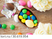 Купить «chocolate egg with candies and cupcakes on table», фото № 30619954, снято 15 марта 2018 г. (c) Syda Productions / Фотобанк Лори