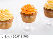 Купить «cupcakes with frosting on confectionery stands», фото № 30619966, снято 6 июля 2018 г. (c) Syda Productions / Фотобанк Лори