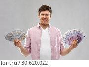 Купить «happy young man with fans of euro and dollar money», фото № 30620022, снято 3 февраля 2019 г. (c) Syda Productions / Фотобанк Лори