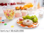 Купить «grapes, macarons and donut on party table», фото № 30620090, снято 6 июля 2018 г. (c) Syda Productions / Фотобанк Лори