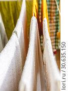 Купить «White and colored linen and towels to be dried on the clothesline», фото № 30635150, снято 2 октября 2018 г. (c) Tetiana Chugunova / Фотобанк Лори