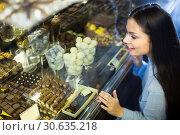 Купить «Smiling girl choosing chocolates», фото № 30635218, снято 31 марта 2020 г. (c) Яков Филимонов / Фотобанк Лори