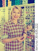 Купить «Female next to shelf with buttons», фото № 30635222, снято 23 мая 2019 г. (c) Яков Филимонов / Фотобанк Лори