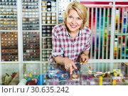 Купить «Mature glad woman seller is ready to help at cash desk», фото № 30635242, снято 24 апреля 2019 г. (c) Яков Филимонов / Фотобанк Лори
