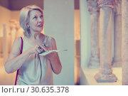 Купить «female visitor with guide book in the museum», фото № 30635378, снято 7 октября 2017 г. (c) Яков Филимонов / Фотобанк Лори