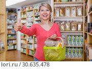 Купить «Mature female customer demonstrating healthy food», фото № 30635478, снято 15 марта 2017 г. (c) Яков Филимонов / Фотобанк Лори
