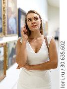 Купить «Woman talking by phone in museum», фото № 30635602, снято 28 июля 2018 г. (c) Яков Филимонов / Фотобанк Лори