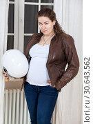 Беременная женщина готова к поездке на мотоцикле. Стоит в комнате у окна. Стоковое фото, фотограф Кекяляйнен Андрей / Фотобанк Лори