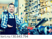 Купить «Adult man displaying his tools for making keys», фото № 30643794, снято 2 февраля 2017 г. (c) Яков Филимонов / Фотобанк Лори