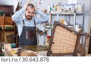 Купить «Annoyed workman in repair furniture workshop», фото № 30643878, снято 19 ноября 2018 г. (c) Яков Филимонов / Фотобанк Лори